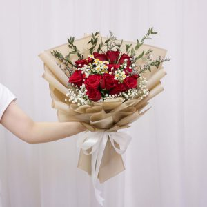 Someone holding a Vin Florist's Golden Red bouquet
