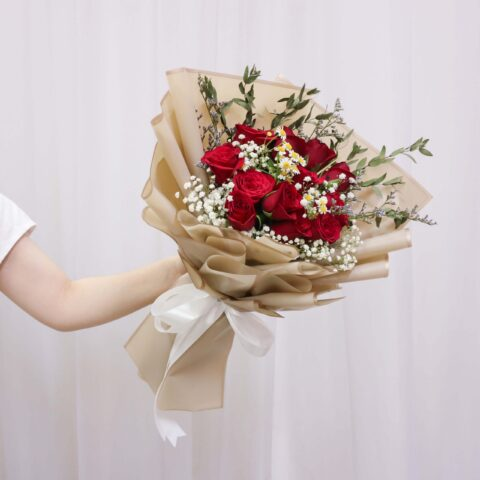 Someone holding a Vin Florist's Golden Red bouquet 2